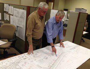 Two men reviewing utility blueprints