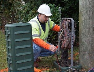Worker installing telephone wiring at junction