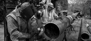 Men standing with grinder - working on gas piping