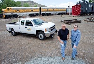 Men standing in front of railroad engine