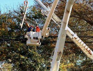 Men working bucket truck performing storm restoration