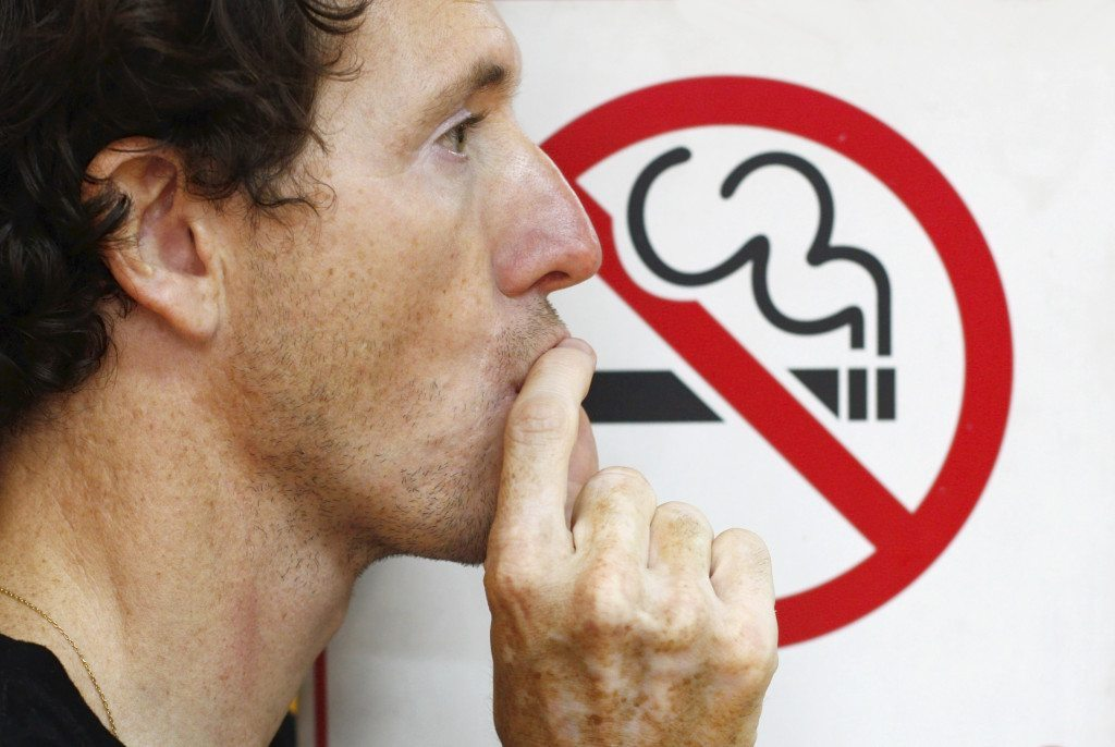 Great American Smokeout - Smoker (man) smoking a no-smoking sign